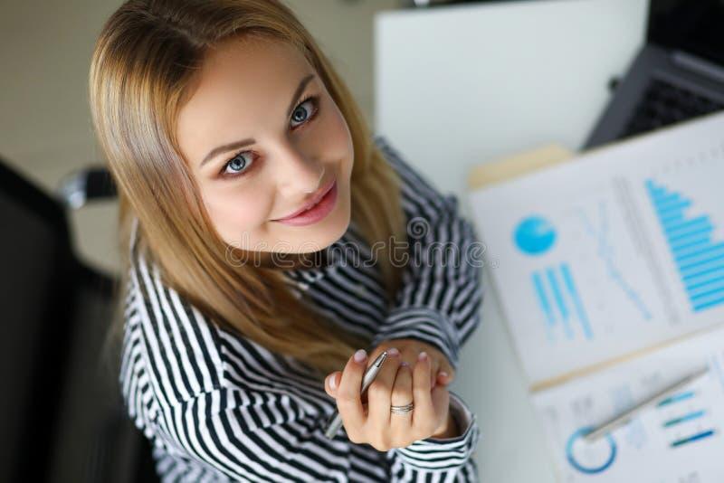 Caixeiro de sorriso bonito que senta-se na tabela de funcionamento imagem de stock