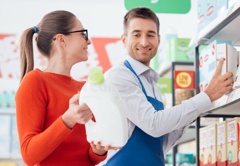 Caixeiro do supermercado que ajuda um cliente foto de stock royalty free