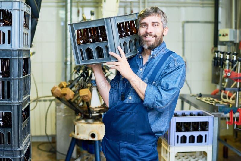 Cajón de la botella de cerveza del trabajador que lleva barbudo imágenes de archivo libres de regalías