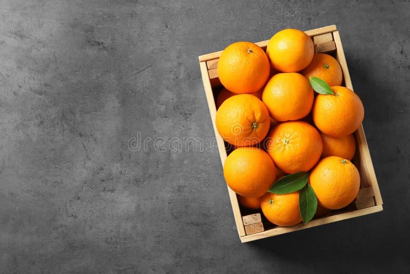 Cajón de madera con las naranjas maduras en fondo gris Espacio para el texto imagen de archivo libre de regalías