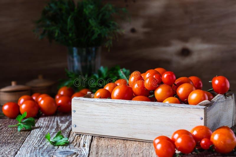 Cajón de tomates de cereza orgánicos recientemente escogidos en la tabla rústica fotos de archivo libres de regalías