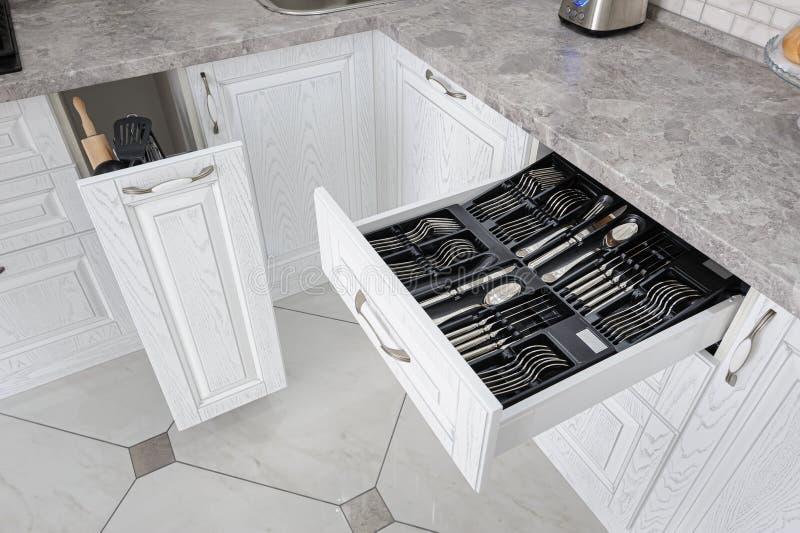 Caj?n con los cubiertos de plata en cocina blanca moderna fotos de archivo
