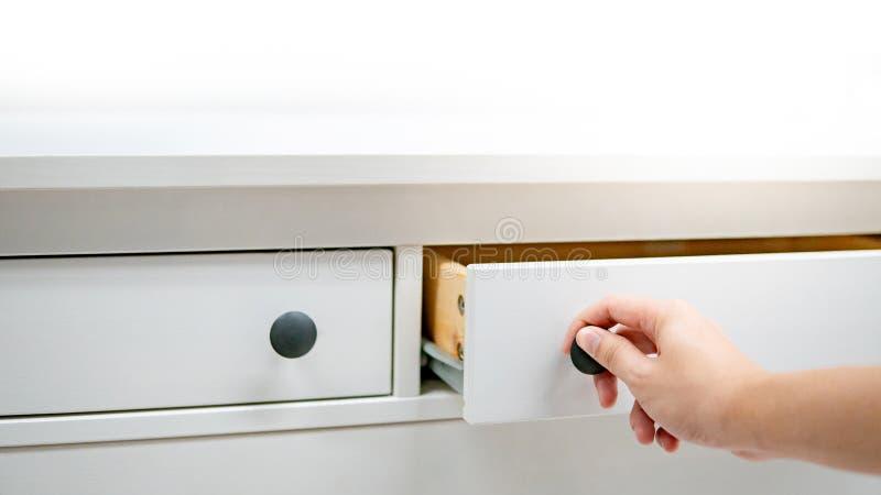 Caj?n masculino de la abertura de la mano en el gabinete blanco imagen de archivo libre de regalías
