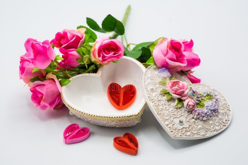 Caja abierta del corazón con mini artesanía dentro con el ramo de la decoración de rosas en el fondo blanco imágenes de archivo libres de regalías