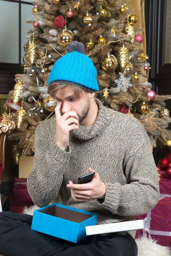 Caja abierta del hombre actual con smartphone en el árbol de navidad fotografía de archivo libre de regalías