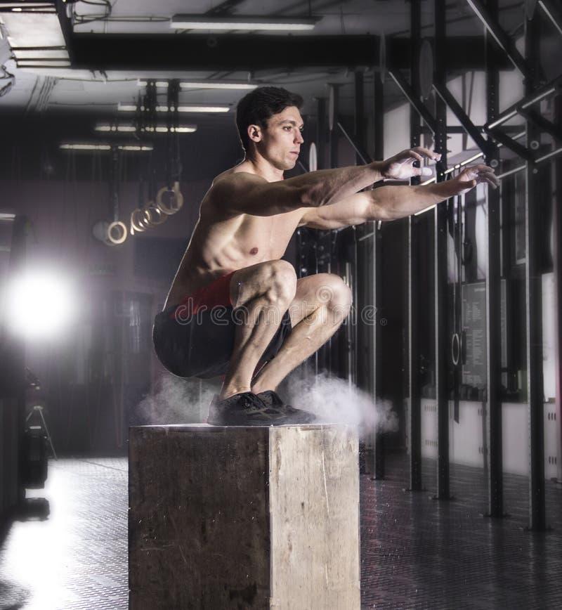 Caja apta del hombre joven que salta en un gimnasio del crossfit El atleta es performin foto de archivo libre de regalías