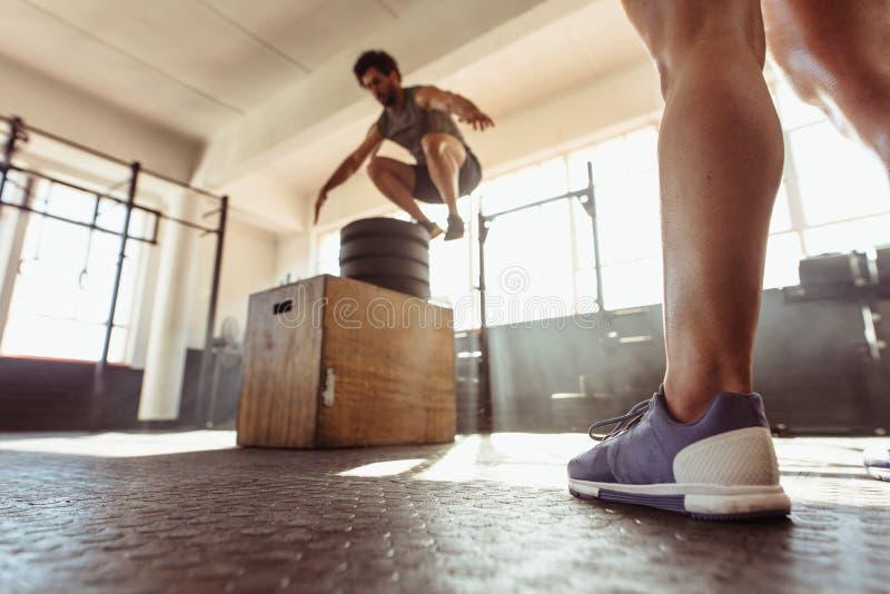 Caja apta del hombre que salta en el gimnasio del entrenamiento cruzado fotografía de archivo libre de regalías