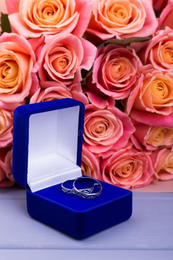 Caja azul con las joyas y las flores anaranjadas imagenes de archivo