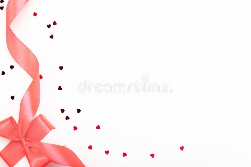 Caja blanca de regalo con un arco rojo sobre fondo blanco Regalo del día de San Valentín con cinta y la vista en forma de corazón imagen de archivo libre de regalías