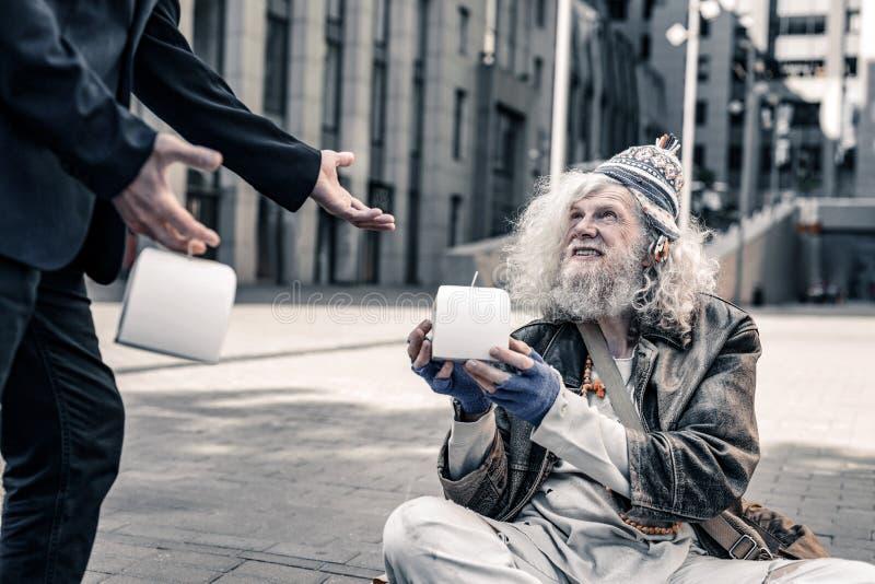 Caja blanca que lleva pobre de emisión del viejo hombre con la comida fresca fotos de archivo