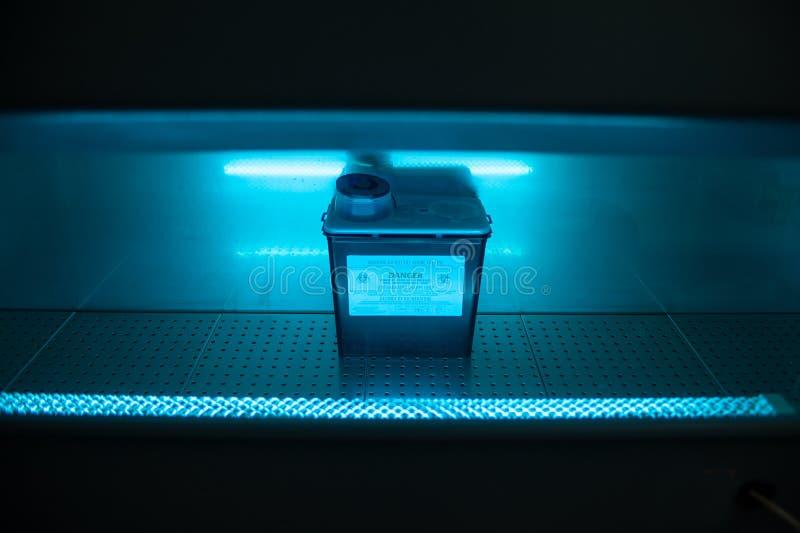 Caja con el contenido del virus del peligro bajo luz ultravioleta ULTRAVIOLETA fotos de archivo