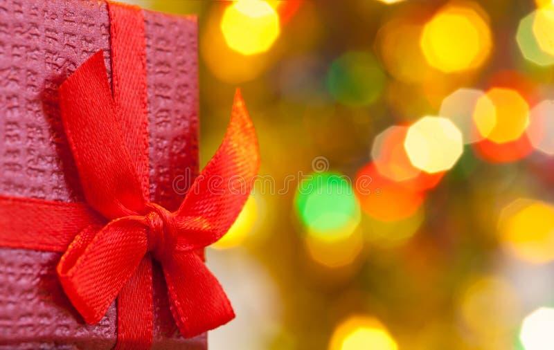 Caja con el regalo de la Navidad con el fondo rojo del día de fiesta del extracto de la luz del arco y del bokeh de la Navidad imágenes de archivo libres de regalías