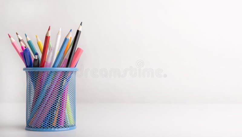 Caja con lápices de colores aislados sobre fondo blanco foto de archivo