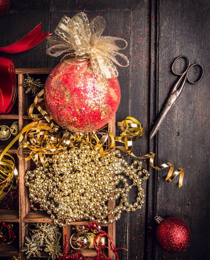 Caja con las decoraciones para los árboles de navidad con las tijeras viejas en fondo de madera oscuro foto de archivo libre de regalías