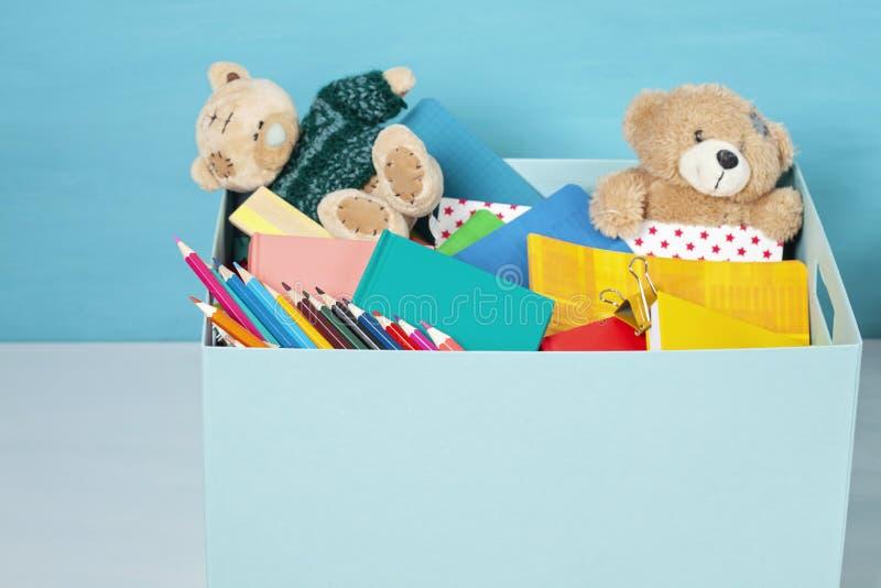 Caja con las donaciones para los niños con las fuentes y los juguetes de escuela fotografía de archivo libre de regalías