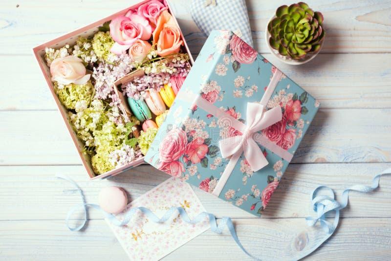Caja con las flores y los macarrones fotos de archivo