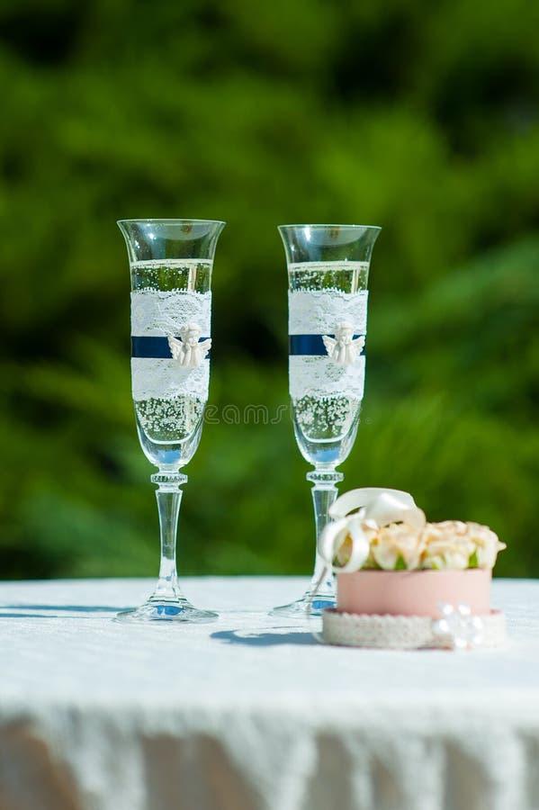 Caja con los anillos de bodas al lado de los vidrios de champán imagenes de archivo