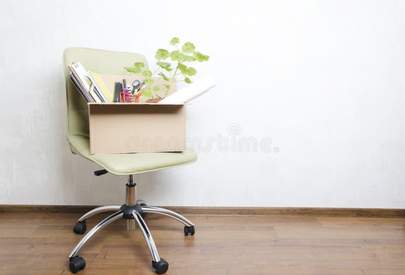 Caja con los artículos personales que se colocan en la silla en la oficina Concepto de mudanza o de despido foto de archivo