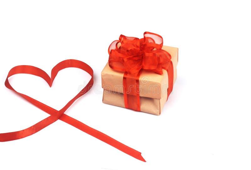 Caja con un regalo, atado con un arco rojo fotografía de archivo