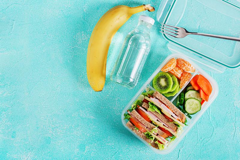 Caja de almuerzo escolar con el bocadillo, las verduras, agua, y las frutas en la tabla fotos de archivo