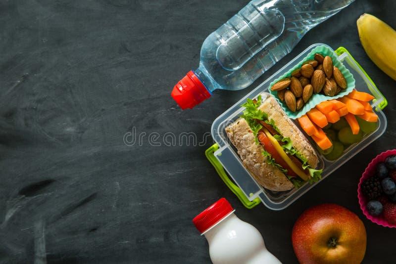 Caja de almuerzo escolar con los libros y los lápices delante del tablero negro foto de archivo