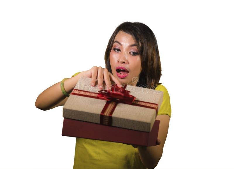 Caja de apertura joven de la Navidad de la mujer indonesia asiática feliz y hermosa o de regalo de cumpleaños con la cinta roja e imagenes de archivo