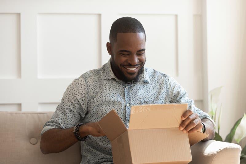 Caja de cartón abierta sonriente del consumidor africano del hombre conseguir el paquete postal fotos de archivo libres de regalías