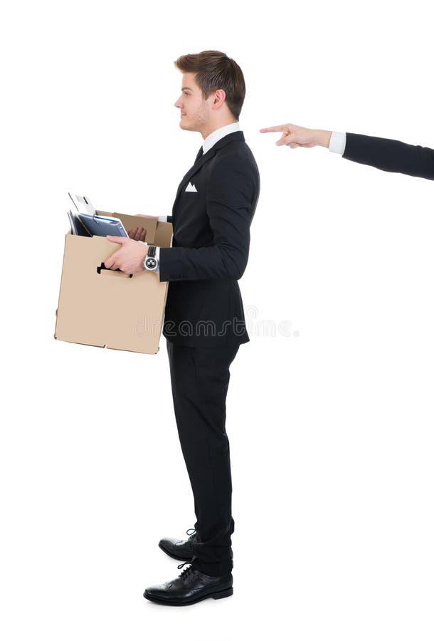 Caja de cartón del hombre de negocios que lleva con la mano que señala en él fotos de archivo libres de regalías
