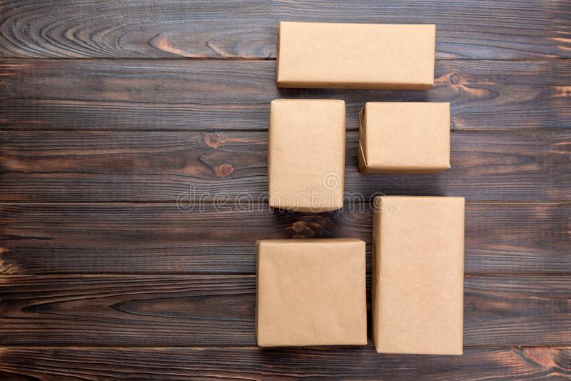 Caja de cartón en el fondo de madera blanco, opinión superior del paquete del correo de Brown imagenes de archivo