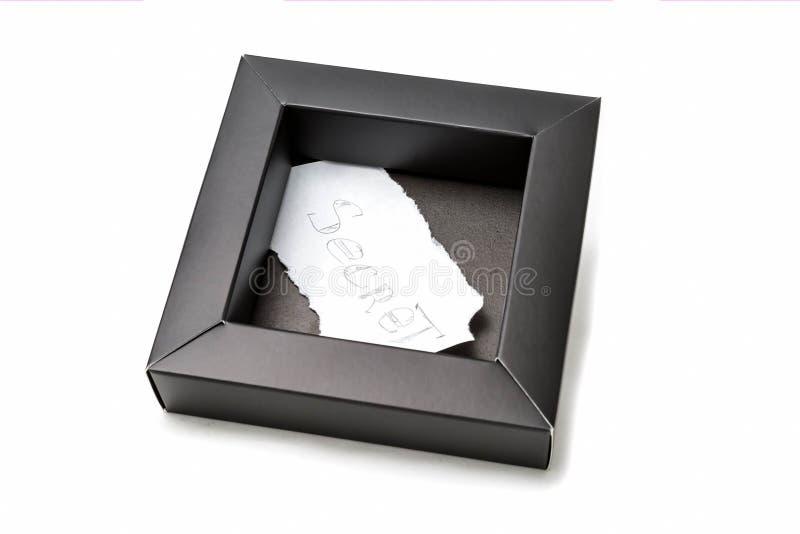 Caja de cartón negra con una hoja de papel dentro que se escribe máximo secreto con un lápiz En un fondo blanco, aislado fotos de archivo libres de regalías