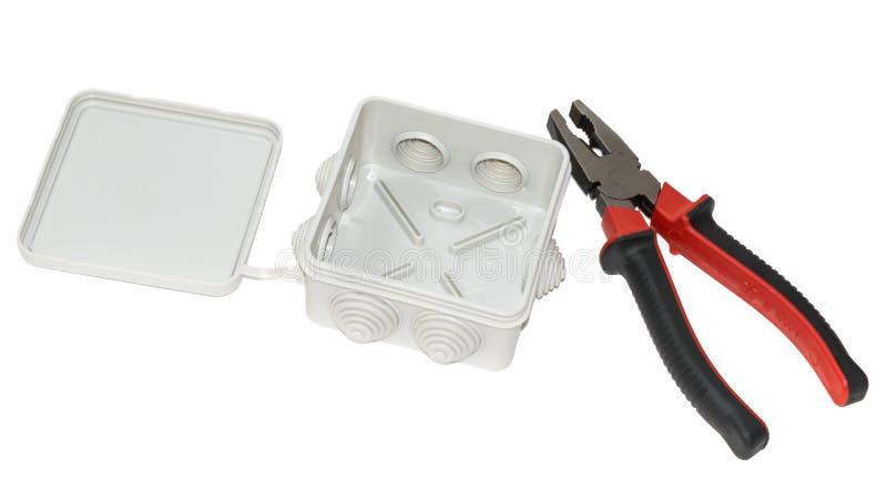 Caja de conexiones y alicates aislados en el fondo blanco imagen de archivo