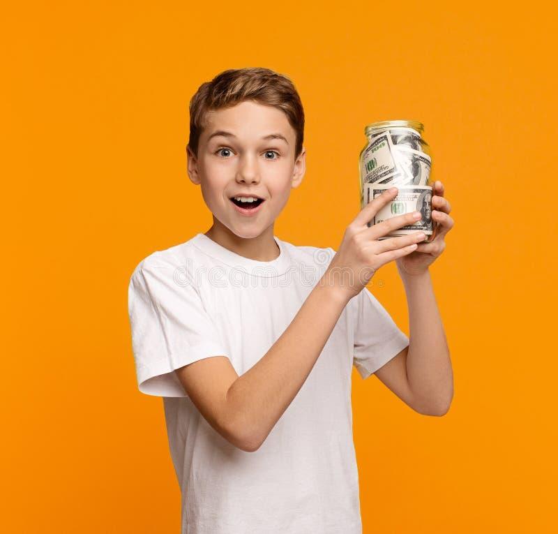 Caja de dinero de cristal de la tenencia emocional del muchacho en fondo anaranjado imágenes de archivo libres de regalías