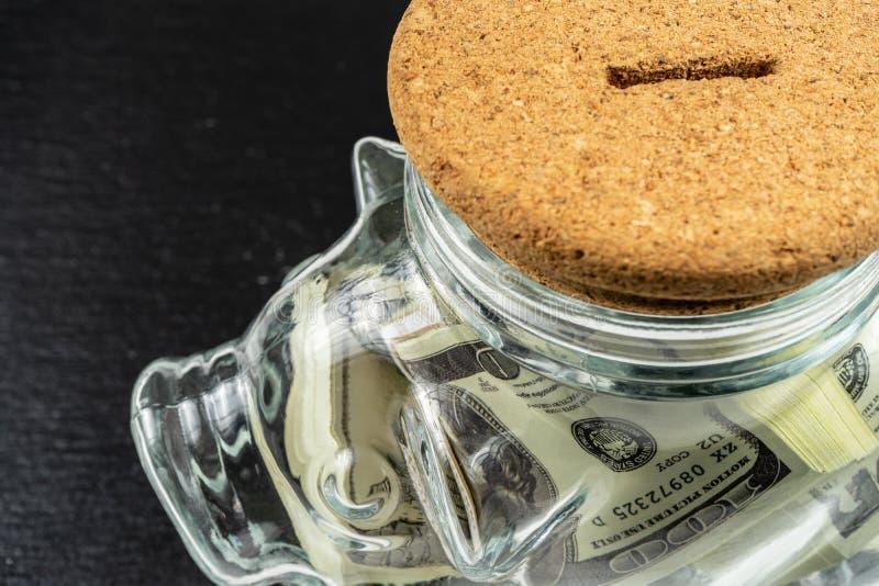 Caja de dinero del banco de cerdo grande,Jar de cristal con ladrillos de 100 dólares estadounidenses,efecto de luz solar foto de archivo