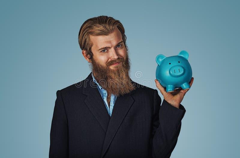 Caja de dinero de hucha de la tenencia del hombre sobre azul imágenes de archivo libres de regalías