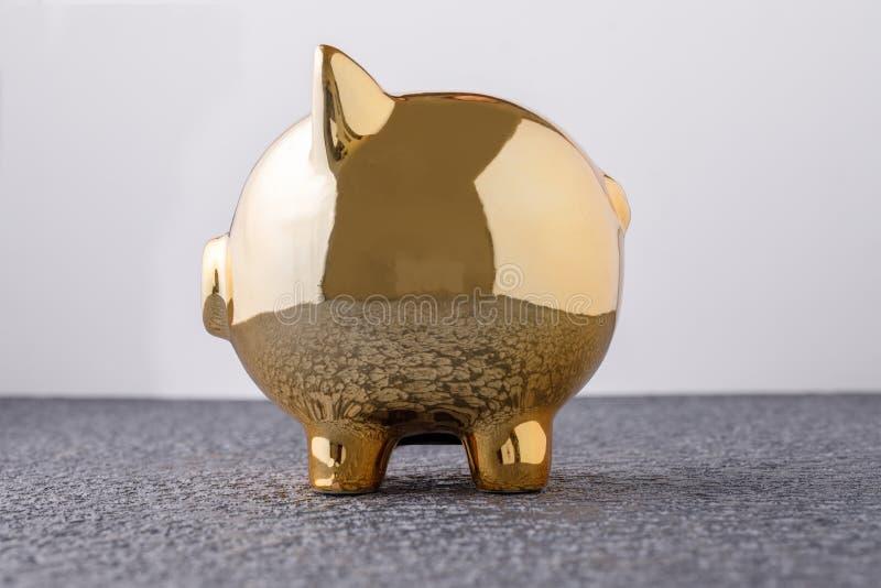Caja de dinero de oro del cerdo en el concepto negro del fondo para el seguro financiero, la protección, la inversión segura o la fotos de archivo
