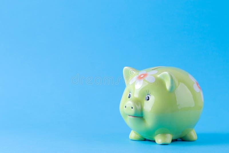 Caja de dinero verde del cerdo en un fondo azul brillante Finanzas, ahorros, dinero Espacio para el texto imagen de archivo libre de regalías