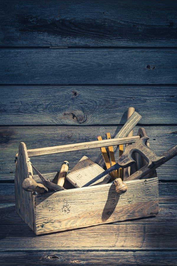 Caja de herramientas vieja de los carpinteros en la tabla de madera rústica fotos de archivo
