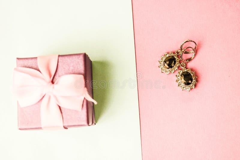 Caja de la belleza, caja de regalo hermosa festiva con un arco con los pendientes de plata con las piedras preciosas en un fondo  imagen de archivo