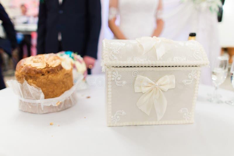 Caja de la boda para los deseos y dinero junto con el pan tradicional en la tabla en la celebración fotos de archivo libres de regalías
