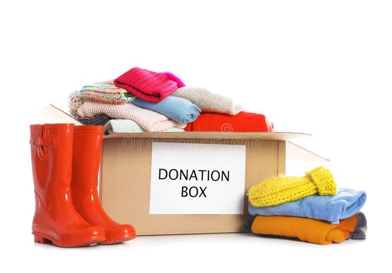 Caja de la donación, botas de goma y ropa foto de archivo