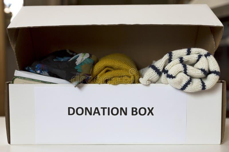 Caja de la donación con ropa y libros fotografía de archivo libre de regalías