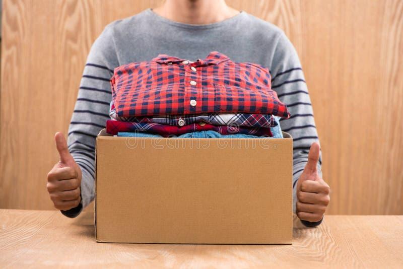 Caja de la donación para los pobres con ropa en las manos masculinas imágenes de archivo libres de regalías