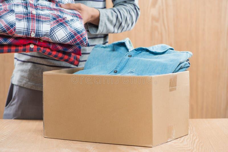 Caja de la donación para los pobres con ropa en las manos masculinas imagen de archivo