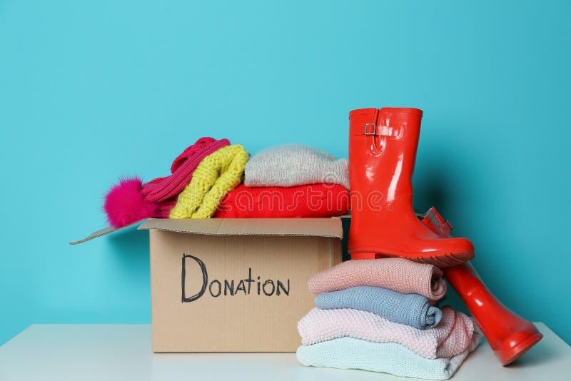 Caja de la donación, ropa hecha punto y botas de goma en la tabla fotos de archivo libres de regalías