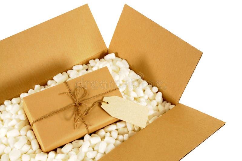 Caja de la entrega de la cartulina con el paquete del correo del papel marrón y la etiqueta de dirección de Manila del espacio en imágenes de archivo libres de regalías