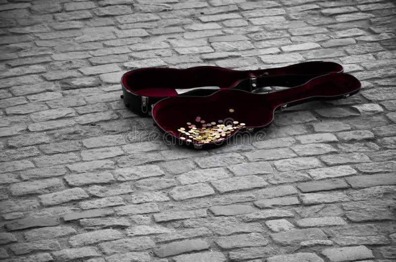 Caja de la guitarra por completo de monedas en las tejas grises imagen de archivo libre de regalías