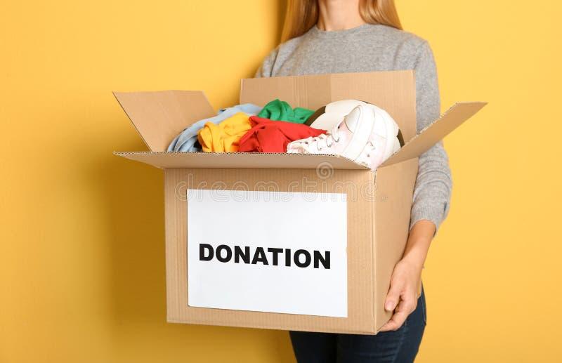 Caja de la tenencia de la mujer con donaciones foto de archivo