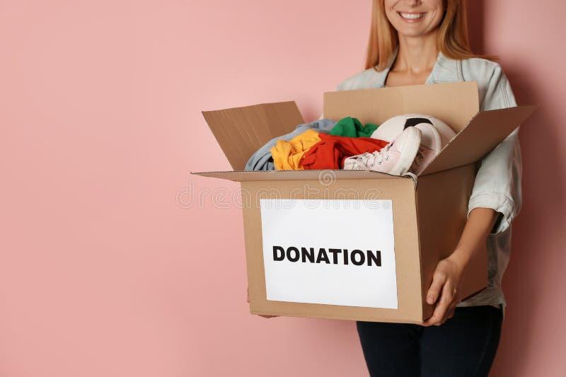 Caja de la tenencia de la mujer con donaciones en fondo del color imagen de archivo