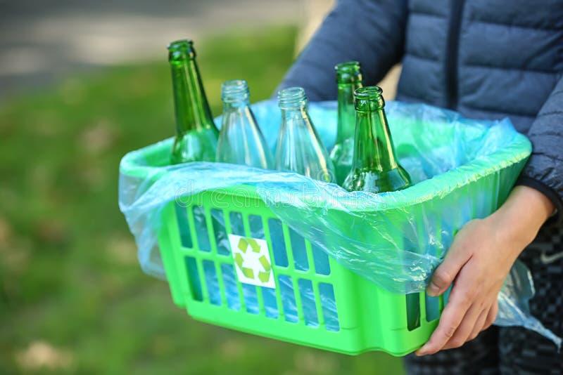 Caja de la tenencia de la mujer con las botellas de cristal vacías al aire libre fotos de archivo libres de regalías