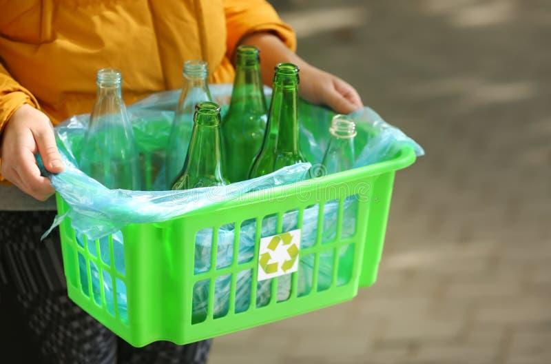 Caja de la tenencia de la mujer con las botellas de cristal vacías al aire libre foto de archivo